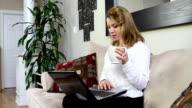 Frau sitzt auf Sofa mit laptop-computer