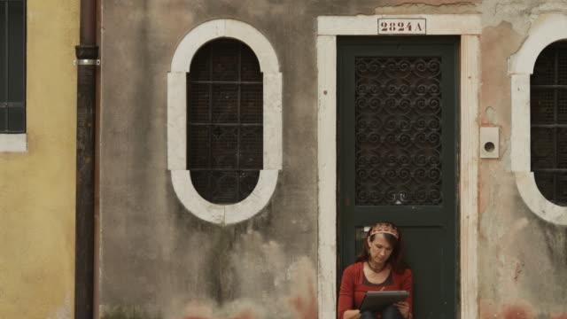 WS TD Woman sitting on doorstep of building,using digital tablet / Venice