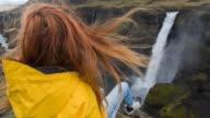 Vrouw zittend op de rand van een canyon, kijken naar waterval