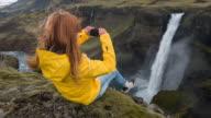 Vrouw zittend op de rand van een ravijn, fotograferen van waterval