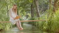SLO MO vrouw zitten on Footbridge based en lezen