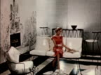 1956 WS Woman sitting on Midcentury Modern white leather couch. She picks up large magazine and starts to read it / USA