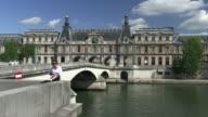 WS Woman sitting on Pont du Carrousel near river seine and reading book / Paris, Ile-de-France, France
