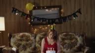 MS TD Woman sitting on sofa blowing candles on birthday cake / Orem, Utah, USA