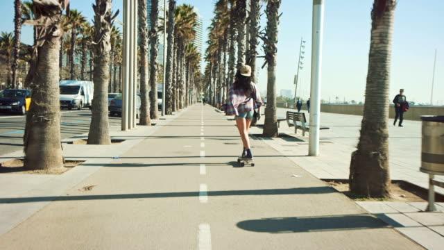 Vrouw skateboarden op strand