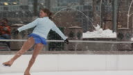 A woman skating at a busy ice rink