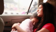 Woman sleeping with her daughter in a car