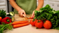Woman slices carrots, vegetables in home kitchen.