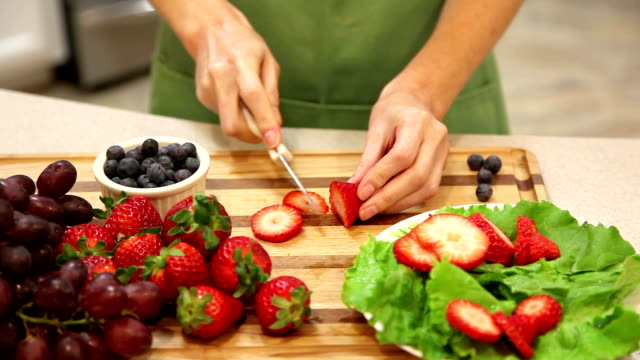 Woman slices strawberries in home kitchen.