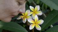 A woman smelling a Frangipani flower