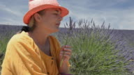 A woman smelling lavender in field