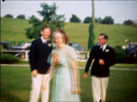 1940 woman smiles at camera outdoors + walks away / 2 men in suits in background / Maplewood, NJ