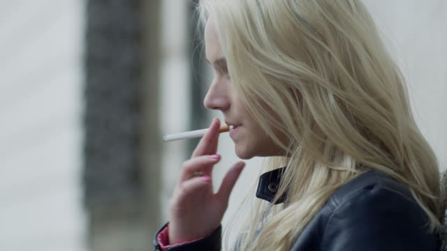 woman smoking a cigarette and coughing