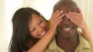 woman sneaking up and covering boyfriend's eyes