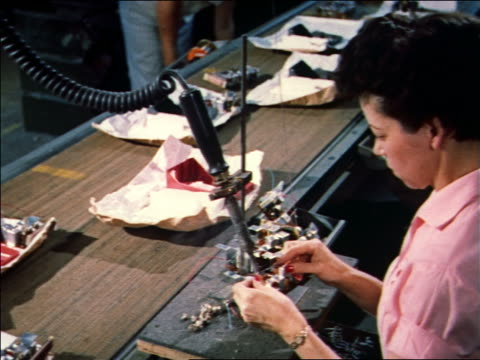 1959 woman soldering small electronic devices on assembly line