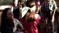 MS woman spins blindfolded girl holding stick for pinata at birthday party / FLASH FRAMES