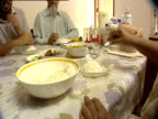 A woman spoons rice from a bowl at a dinner table