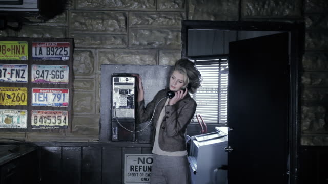 MS Woman standing at old style payphone in gas station or hotel / Palmdale, CA, United States