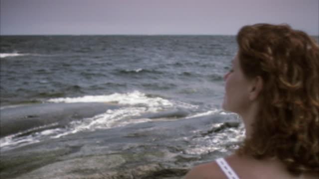 A woman standing by the sea Huvudskar Stockholm archipelago Sweden.