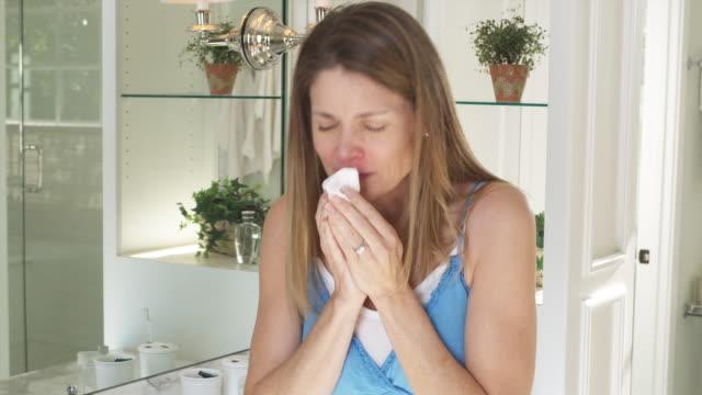 MS Woman standing in bathroom sneezing into tissue, Phoenix, Arizona, USA