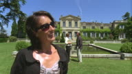 CU, TU, Woman standing in front of palace, man and woman talking in background, Saint Ferme, Gironde, France
