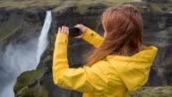 Vrouw stond op een klif, met foto's van de waterval met smartphone