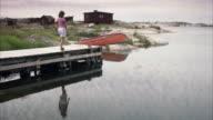A woman standing on a jetty Huvudskar Stockholm archipelago Sweden.