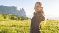 Vrouw staande op een zon bedekt weide, kijken naar het gebergte