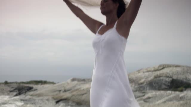 A woman standing on  cliffs by the sea Huvudskar Stockholm archipelago Sweden.