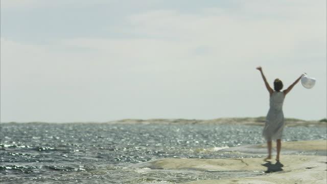 A woman standing on cliffs Huvudskar Stockholm archipelago Sweden.