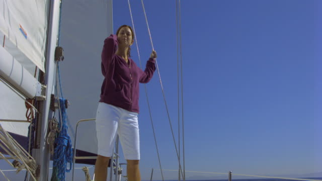 WS Woman standing on deck of yacht and smiling, looking out to sea / Santa Barbara, California, USA