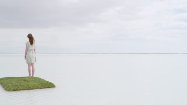 MS PAN Woman standing on small grass island in large body of water looking out