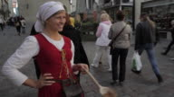 MS Woman standing on street giving samples of roasted almonds / Tallinn, Estonia