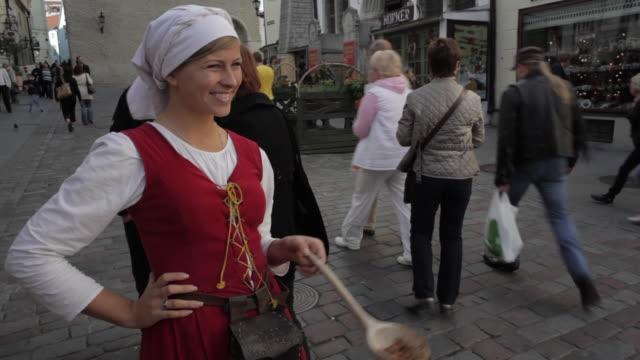 MS Woman standing on street giving samples of roasted almonds / Tallinn, Estonia