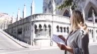 Woman stands below gothic cathedral, holding map