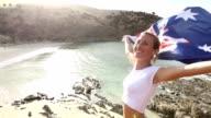Kvinna står på en klippa ovanför stranden håller australiska s flagga