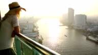 Donna si trova sulla HIGH-rise solarium, si affaccia sulla città e sul fiume