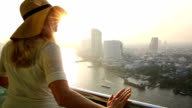 Frau steht auf hoher Leibhöhe, Terrasse, Blick auf die Stadt, den Fluss