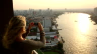 Woman stands on hi-rise deck, takes pic of city, river