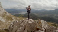 Woman stands up over the to of a mountain