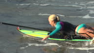 A woman stand-up paddleboard surfing at the beach. - Slow Motion