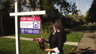 MS PAN Woman sticking 'Sold' sign in front of suburban house / Provo, Utah, USA