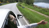 POV of woman stretches arm out car window, by lake