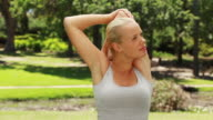 Woman stretching her arms and then looking at the camera and smiling