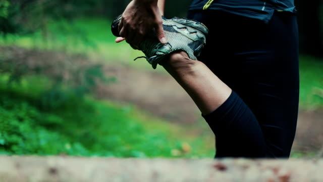 Kvinnan sträcker sig i skogen efter löpning