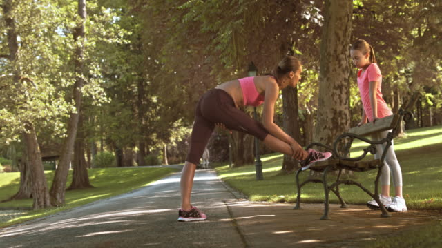 DS Woman stretching on a park bench and talking to her daughter