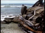 Cornwall Wreckage of Vauxhall Nova car on rocky shore PULL OUT as waves crash onto beach MS Wreckage of car lying on roof TILT DOWN MS Mangled...