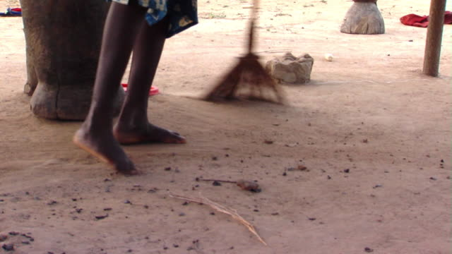 CU Woman sweeping dusty ground, Tamale, Ghana
