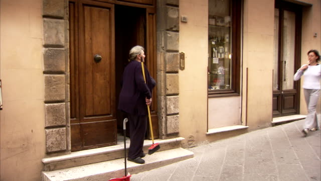 A woman sweeps the steps at the entrance of her apartment building. Available in HD.
