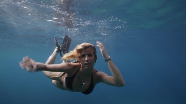 MS, SLO MO A woman swims underwater towards camera / Ibiza, Spain